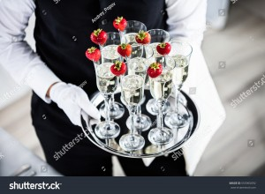 stock-photo-waiter-standing-with-champagne-glasses-next-to-arranged-wedding-table-555965092
